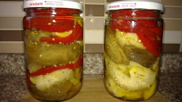 Malzemeler: 3 ya da 4 kilo patlıcan (aslında siz ne kadar isterseniz o kadar alın) 2 baş sarmısak iri tuz (kaya tuzu) zeytin yağı yarım kiloluk veya birer kiloluk cam kavanoz   Hazırlanışı: Patlıcanlarımızı eğer ateş yakma imkanımız varsa ateşte közleyelim. Yoksa da sorun değil ocakta veya fırında da soldurmanız mümkün. Soldurduğumuz patlıcanları soyalım. Sap kısımlarını keselim. İster küçük küçük doğrayıp ister de tüm tüm bir kaba alalım. Sarmısağı soyalım ve biraz tuz ile iyice ezelim. Ezdiğimiz sarmısakları patlıcanların üzerine ekleyip iyice patlıcanları ve sarmısakları harmanlayalım. Bu işlemi yapmadan evvel tuz ihtiyacına göre biraz daha tuz ilave edelim. Kavanozların üzerinden 1.5 parmak eksik kalacak şekilde patlıcanları kavanozlara dolduralım. Eksik kalan kısmını zeytinyağı ile doldurup kavanozların kapaklarını sıkı sıkı kapatalım. Bir tencereye su koyup kaynamaya bırakalım. Kaynamaya başladıktan sonra altını kısalım ve kavanozu ters çevirip bu suyun içerisinde 10 dakika kadar bekletelim. Bu şekilde kavanozumuzun kapağının iyice kapanmasını sağlamış oluyoruz. Sudan çıkardıktan sonra yine ters bir şekilde  soğumaya bırkalım. Soğuduktan sonra uygun bir yerde saklayabiliriz. Afiyet olsun.    M.T.'nin Dokunuşu: Kavanozu ters çevirip suda kapağın sıkışmasını beklerken eğer sızıyorsa kavanozu çıkarıp yeni bir kapak kapatıp tekrar suya koyalım.  Dilerseniz bu konserveyi yaparken sarmısak eklemeyebilirsiniz. Közelnmiş patlıcanımızı saklamanın bir diğer yöntemi de hiç bir ek malzeme kullanmadan sadece közlenmiş patlıcanları bie buzdolabı poşetine koyup poşetin ağzını bağlayıp derin dondurucuda saklamak.  İlgili Terimler : Kış hazırlıkları, Kışlık yiyecek saklama, Konserve nasıl yapılır, Közlenmiş patlıcan, Közlen